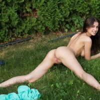 naked girl sunbathing at home on the lawn