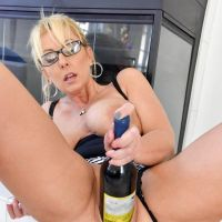 a wine bottle stuck in a pussy milf